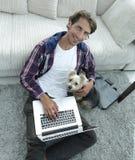 Tipo bello con il computer portatile che abbraccia il suo cane e che si siede vicino allo strato Immagine Stock Libera da Diritti