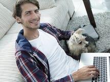 Tipo bello con il computer portatile che abbraccia il suo cane e che si siede vicino allo strato Immagine Stock