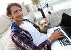 Tipo bello con il computer portatile che abbraccia il suo cane e che si siede vicino allo strato Fotografia Stock Libera da Diritti