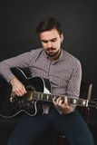 Tipo bello con la chitarra acustica della tenuta della barba Immagine Stock Libera da Diritti