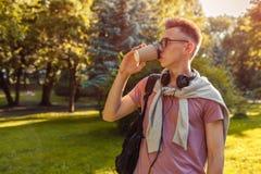 Tipo bello dell'istituto universitario che raffredda nel parco della città universitaria di primavera Caffè bevente dello student Fotografia Stock Libera da Diritti