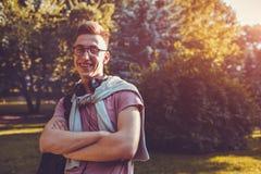 Tipo bello dell'istituto universitario che raffredda nel parco della città universitaria di primavera Lo studente felice dell'uom Immagini Stock