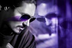 Tipo bello in occhiali da sole con la riflessione Immagine artistica ultravioletta alla moda Immagine composita con in bianco e n immagine stock