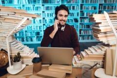 Tipo bianco circondato dai libri in biblioteca Lo studente sta utilizzando il computer portatile e sta parlando sul telefono Immagini Stock