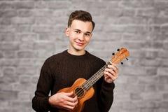 Tipo bianco del ritratto giovane nel gioco del maglione sulle ukulele in sue mani, sul fondo del muro di mattoni fotografia stock