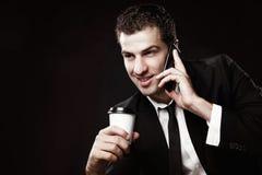 Tipo brutale in un vestito nero con un caffè e un telefono fotografie stock libere da diritti