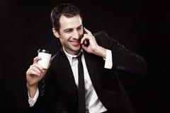 Tipo brutale in un vestito nero con un caffè e un telefono fotografie stock