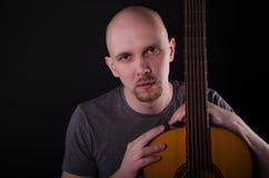 Tipo calvo piacevole con una chitarra Fotografia Stock