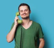 Tipo in camicia con il telefono di quadrante verde Immagini Stock Libere da Diritti