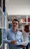 Tipo castana bello che distoglie lo sguardo e che sta accanto al libro Fotografia Stock