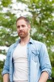 Tipo casuale con una camicia del denim in un parco Fotografie Stock Libere da Diritti