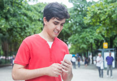 Tipo caucasico bello nel messaggio di battitura a macchina della camicia rossa con il telefono dentro Fotografie Stock Libere da Diritti