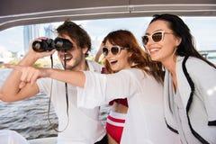 Tipo che esamina binocularus con due ragazze fotografia stock libera da diritti