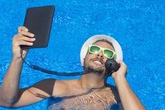 Tipo che ha una chiamata da una piscina fotografia stock