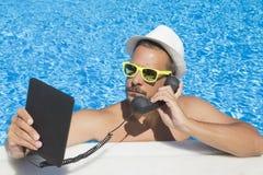 Tipo che ha una chiamata di Internet dalla piscina immagine stock