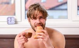 Tipo che mangia caff? ed il croissant delle tenute mentre letto di disposizione in camera da letto o nella camera di albergo Uomo immagine stock libera da diritti