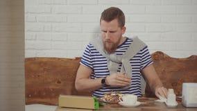 Tipo che mangia dessert e che si siede online in caffè archivi video