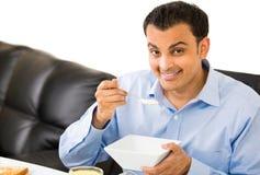 Tipo che mangia prima colazione all'interno Immagini Stock