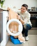 Tipo che mette i vestiti dentro alla lavatrice Fotografia Stock Libera da Diritti