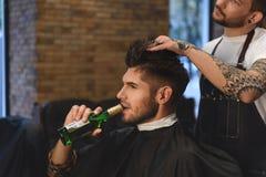 Tipo che ottiene taglio di capelli mentre bevendo fotografia stock libera da diritti