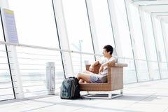Tipo che riposa nel salotto dell'aeroporto Fotografie Stock