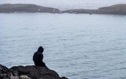 Tipo che si siede su una roccia che esamina le guarnizioni guarnizioni che mettono sulle rocce fotografia stock