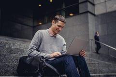 Tipo che si siede sui punti e che lavora con il computer portatile Immagine Stock Libera da Diritti