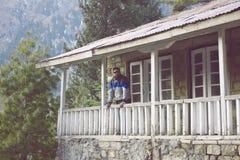 Tipo che sta sul terrazzo di un cottage in montagna fotografia stock libera da diritti