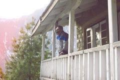 Tipo che sta sul terrazzo di un cottage in montagna immagine stock