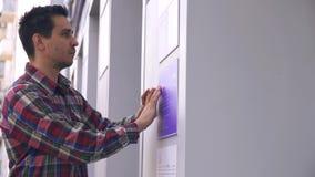 Tipo cieco sulla via che legge una fonte di Braille su un segno della costruzione archivi video