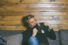 Tipo con i caschi di musica e vinile in sue mani fotografia stock libera da diritti
