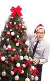 Tipo con il cappello di Santa che fa una pausa un albero di Natale Fotografia Stock Libera da Diritti