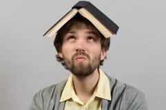 Tipo con il libro sulla testa che pensa sopra il grey Immagine Stock