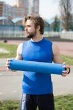 Tipo con l'ente muscolare, l'yoga della tenuta della barba o la stuoia di forma fisica Immagini Stock