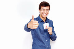 Tipo con le carte e pollice sul segno Immagini Stock