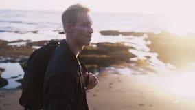 Tipo con le passeggiate dello zaino lungo la spiaggia di sabbia nera al tramonto, chiarore della lente Colpo di Steadicam, movime video d archivio