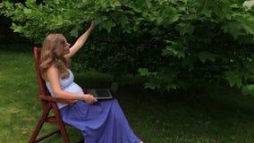 Tipo da mulher gravida com o teclado do portátil que senta-se na cadeira de madeira vídeos de arquivo
