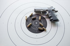 Tipo de 45 balas no alvo do bullseye com pistola borrada Imagem de Stock