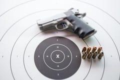 Tipo de 45 balas no alvo do bullseye com pistola borrada Fotografia de Stock Royalty Free