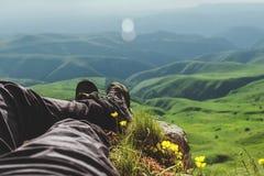 Tipo de botas de la primera persona en las montañas imagenes de archivo