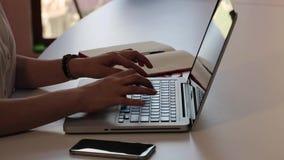 Tipo de la chica joven en el teclado en el ordenador portátil en el ambiente de la oficina metrajes