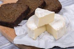 Tipo del brie de queso Queso del camembert Queso fresco del brie y una rebanada en un tablero de madera con la rebanada del pan n Fotografía de archivo