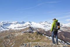 Tipo dell'alpinista che guarda le montagne nevose Fotografia Stock Libera da Diritti
