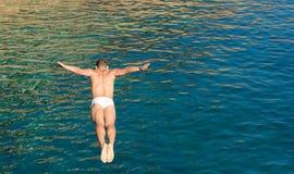 Tipo dell'operatore subacqueo della scogliera che salta nel mare blu dall'alta parete delle rocce Fotografie Stock Libere da Diritti