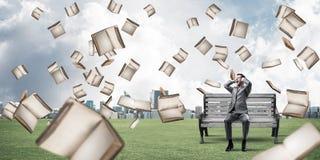Tipo dello studente e da sopra che cadono di molti vecchi libri che si siede su Ben Immagine Stock Libera da Diritti