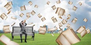 Tipo dello studente e da sopra che cadono di molti vecchi libri che si siede sul banco Fotografia Stock Libera da Diritti