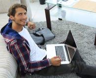 Tipo di affari con il computer portatile che si siede sul tappeto in salone Immagini Stock