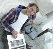 Tipo di affari con il computer portatile che si siede sul tappeto in salone Fotografia Stock Libera da Diritti