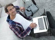Tipo di affari con il computer portatile che si siede sul tappeto in salone Fotografie Stock Libere da Diritti