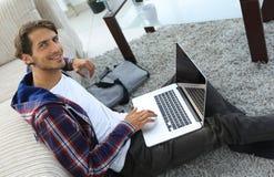 Tipo di affari con il computer portatile che si siede sul tappeto in salone Fotografia Stock